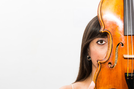 Woman playing violin in studio with white background. With red dress. A classic musical instrument for orchestra. Classical music as a soul care.