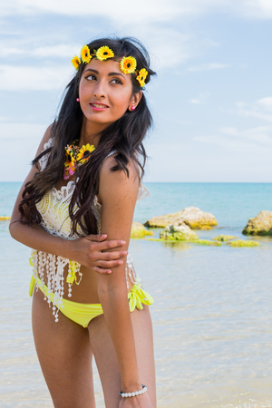 Girl on the beach with crown of flowers yellow bathing suit. Happy and smiling, sunbathing sunbathing, the beach between the rocks. Stock Photo