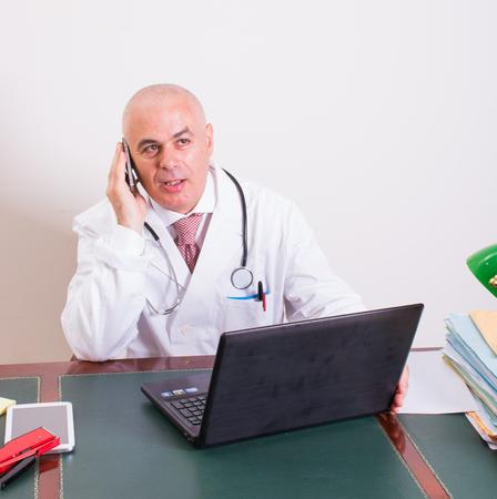 그의 스튜디오에서 Aback 의사는 자신의 노트북 앞에 스마트 폰을 사용합니다. 새로운 기술을 사용하십시오. 그의 전문 스튜디오에서, 그는 골동품 책상