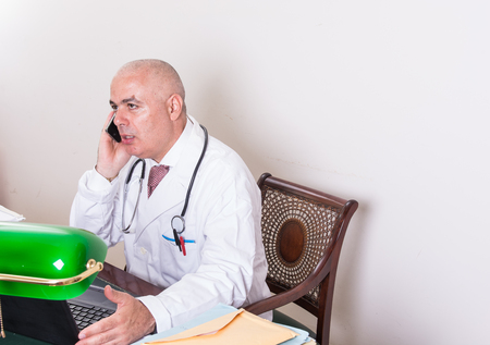 Aback doctor in his studio, uses a smartphone in front of his laptop. Use new technologies. In his professional studio, he is sitting at antique desk, and a green lamp shade of green.