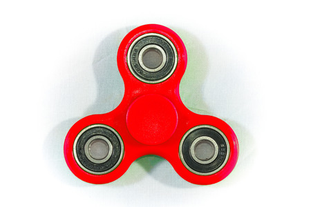 Fidget Spinner in white isolated background. The fidget spinner is a toy, a small spit, the rotating body is pivoted on a ball bearing which allows it to rotate on the axis of rotation.
