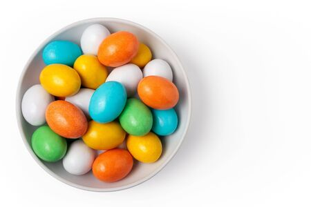 colorful candy eggs in white bowl isolated on white background photo
