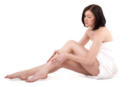 Woman massaging legs sitting on white background Stock Photo