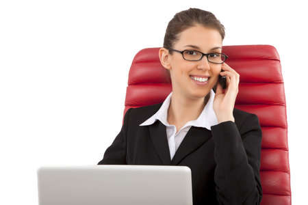 Beautiful business woman talking on mobile phone sitting on a red chair in office photo