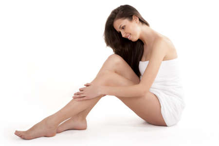 Woman massaging legs sitting on white