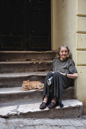 Old Senior Homeless Woman sitting on the street with her cat in Poverty