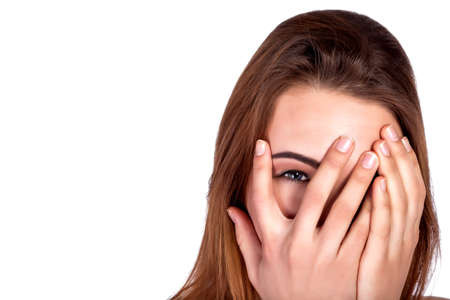 Beautiful young girl peeking through fingers