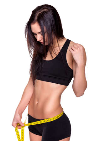 Young Beautiful Attractive Gym Woman Measuring Her Waist photo
