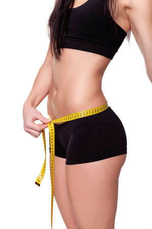 woman measuring: Young Woman measuring her waist - Stock Image