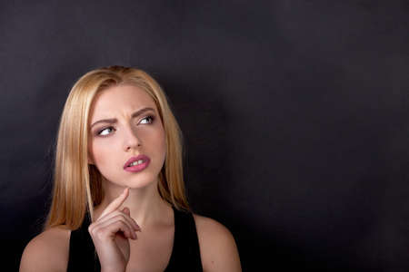 20 29 years: Contemplative thinking woman student at a black background - Stock Image