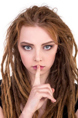Shhhhh - dreadlocks woman finger on lips - Stock Image Stock Photo