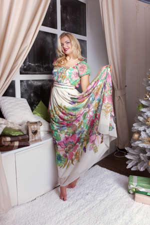 Blonde woman in beautiful dress christmas time - Stock Image