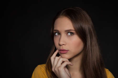 20   24: Contemplative thinking woman student at a black background - Stock Image