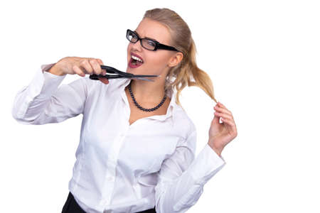 Angry businesswoman cutting her hair with scissors at office - Stock Image
