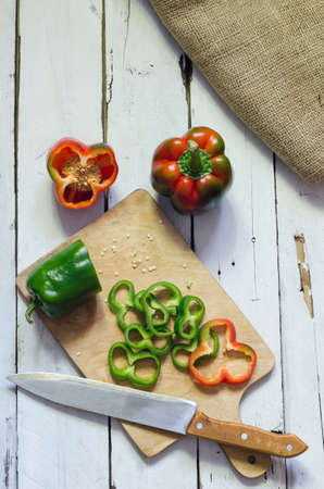 green top: Photo of sliced colorul peppers over white wooden table