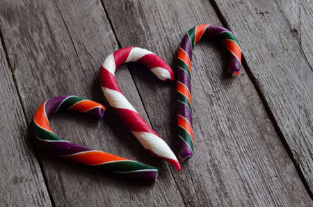 stuffer: Three colourfull candy canes on a wooden background.
