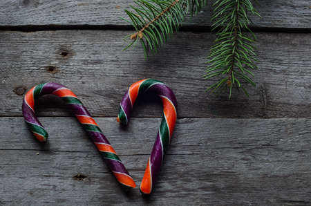 Three colourfull candy canes on a wooden background.