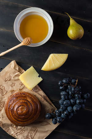 Morning breakfast. Bun, cheese, swet honey and fruits. Homemade traditional food Zdjęcie Seryjne - 87965015