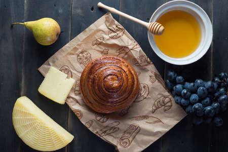 Morning breakfast. Bun, cheese, swet honey and fruits. Homemade traditional food Zdjęcie Seryjne - 87951182