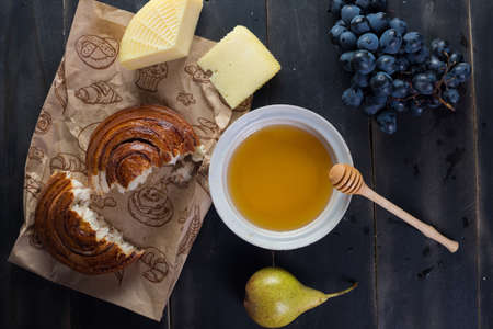 Morning breakfast. Bun, cheese, swet honey and fruits. Homemade traditional food Zdjęcie Seryjne - 87959939
