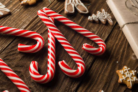 Chrismas cookies, candy canes on wooden background. Holiday mood. Top view.
