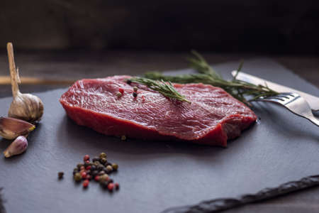 Raw beef steak with rosemary, peppers garlik on dark stone, fork and knife