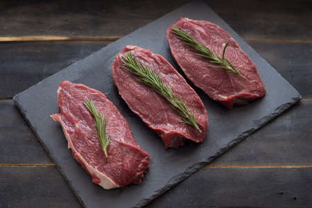 Raw meat, beef steak with rosemary on black background. Three items.