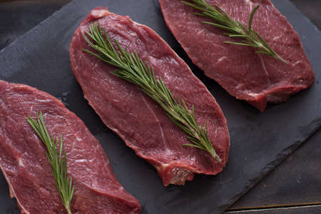 Raw meat, beef steak with rosemary on black background. Three items. Close up.