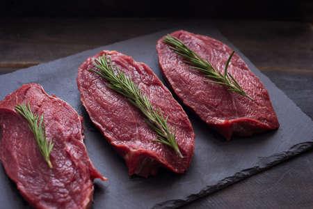 Raw meat, beef steak with rosemary on black background. Three items. Close up. Zdjęcie Seryjne - 94488657