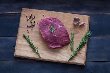 Raw beef steak with rosemary, peppers garlik on woden board