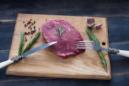 raw beef steak with rosemary and peppers on wooden board
