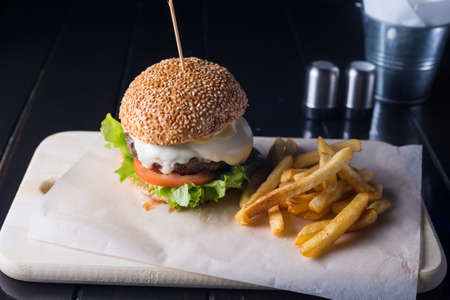 fresh tasty burger and french fries on wooden board, meat and cheese