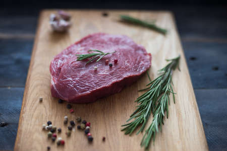 raw beef steak with rosemary and peppers on wooden board Zdjęcie Seryjne - 94488659