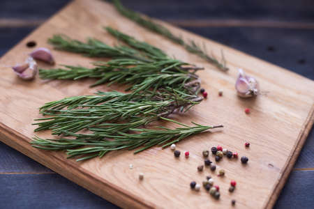 Rosemary plant on wooden rustic table from above, fresh organic herbs, peppers