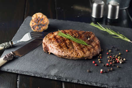 Grilled beef steak on stone plate over wooden table with fork and knife.