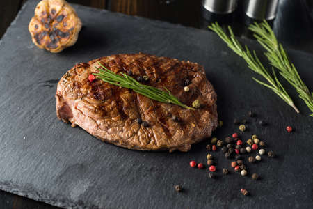 Grilled beef steak on stone plate over wooden table with fork and knife. Zdjęcie Seryjne - 94657004
