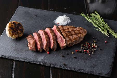 Sliced prime ribeye steak on black stone plate. Medium degree of steak doneness. With rosemary and peppers. Fork and knife. Zdjęcie Seryjne - 94708612