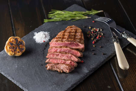 Sliced prime ribeye steak on black stone plate. Medium degree of steak doneness. With rosemary and peppers. Fork and knife. Zdjęcie Seryjne - 94708615