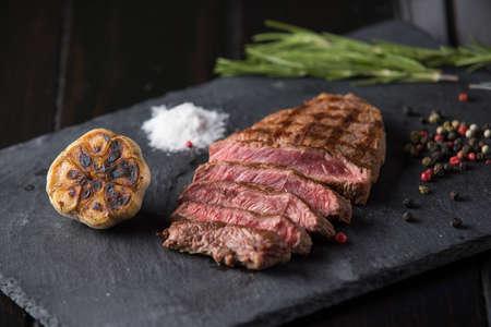 Prime Black Angus Ribeye steak on black stone plate. Medium degree of steak doneness. Top view.