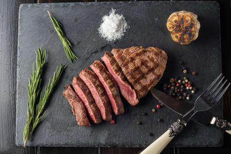 Prime Black Angus Ribeye steak on black stone plate. Medium degree of steak doneness. Top view. Zdjęcie Seryjne - 94708620