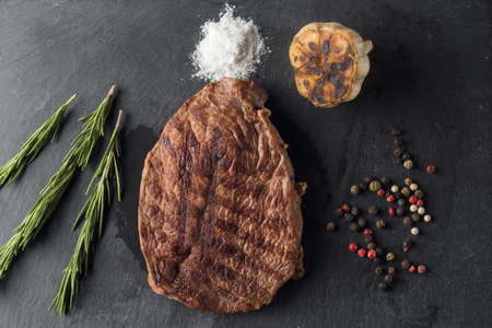 Grilled beef steak on black stone plate over wooden table with fork and knife Zdjęcie Seryjne - 94708625