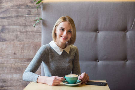 Woman drinking coffee in the morning at restaurant. Soft focus on the eyes. Sellphone on table.