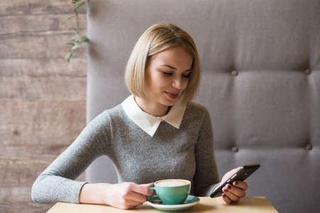 Young woman at cafe drinking coffee and using smartphone