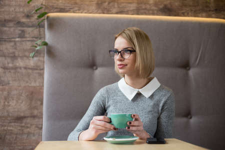 Young business woman in glasses sits in a cafe at a table, drinks coffee, holds smartphone in her hand. The girl is having breakfast in the restaurant,waiting for friends, colleagues. Zdjęcie Seryjne - 95450912
