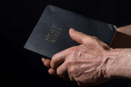 Aged man's hands holding the Bible. Black background. Zdjęcie Seryjne - 98688667