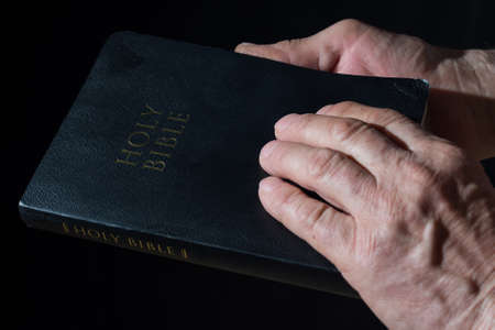 Aged man's hands holding the Bible. Black background.