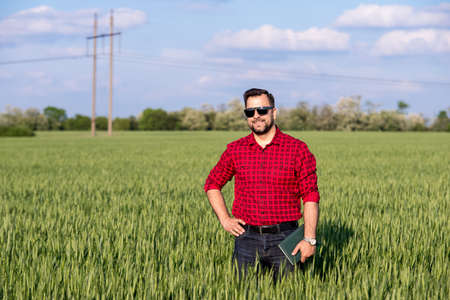 Young handsome farmer with diary standing in wheat field Standard-Bild