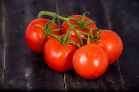 tomatoes on wooden background. Branch of ripe tomatoes on black wooden background. Standard-Bild