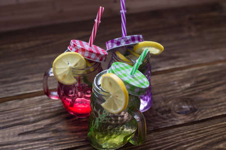 lemonade in jar with ice and mint, different colors of jars