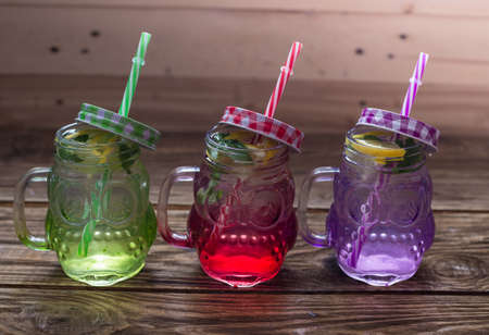 lemonade in jar with ice and mint, different colors of jars Zdjęcie Seryjne - 106663645